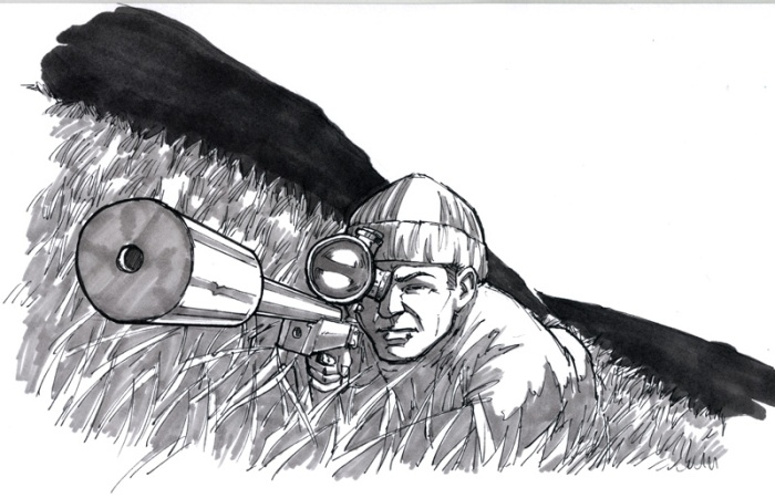 A Sniper hides in the long grass & take a deep breath before pulling the trigger.